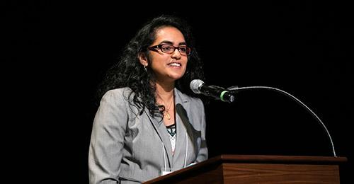 Ambika Siddabathula speaking at a podium.