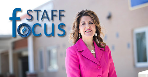 Kimberlyn Pratesi standing in front of school with staff focus logo in foreground.