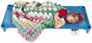 a girl sleeps on a blue cot, a colorful quilt is tucked around her