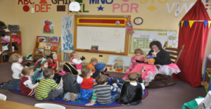 Circle time for a group of 4 year olds. Many of the children are dressed in costume. The teacher sits on a rocking chair reading, her lap covered by a blanket. A child sits beside her on another chair. Behind the chairs is a hanging tent.