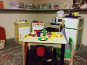 A play kitchen is set up in the corner of the classroom. The wall is lined with a continuous self with several pieces of artwork. Below are several cabinets and a refrigerator with play food and kitchen supplies. In the center of the space is a table covered with various play food things and surrounded by four brightly colored chairs.