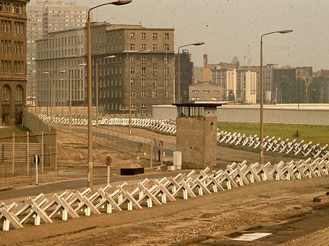 "The ""death strip"" on the East Berlin side of the Wall, with anti-tank ""Czech Hedgehog"" barriers and a guard tower, fall of berlin wall - HeadStuff.org"