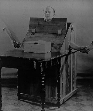 Harry Houdini in a wooden box designed to restrict a medium's movement - headstuff.org