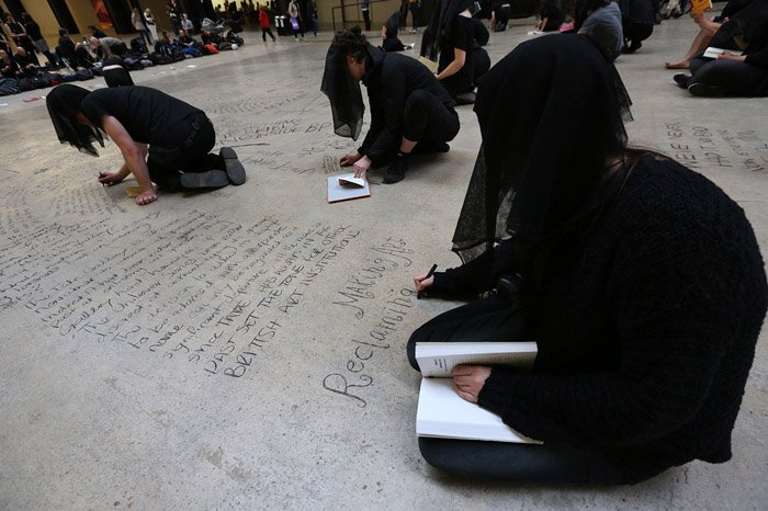 Performers writing on the floor of the museum-Headstuff.org