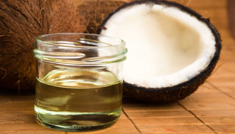 Image of jar of coconut oil beside half a coconut, one of the symbols of the clean eating movement.