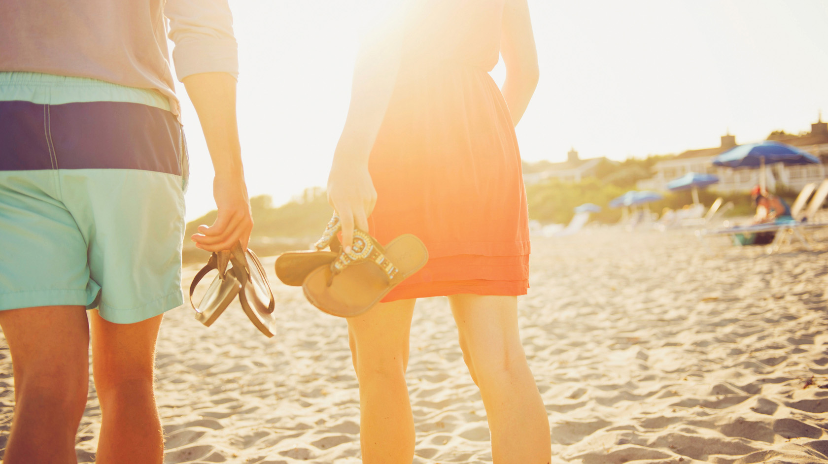 couple walking along beach with shoes in hand in Rhode Island