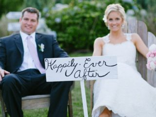 bride and groom pose with sign in Newport RI