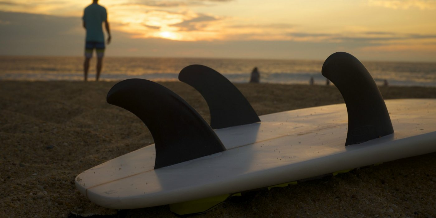 Surfboard with man in background sunset