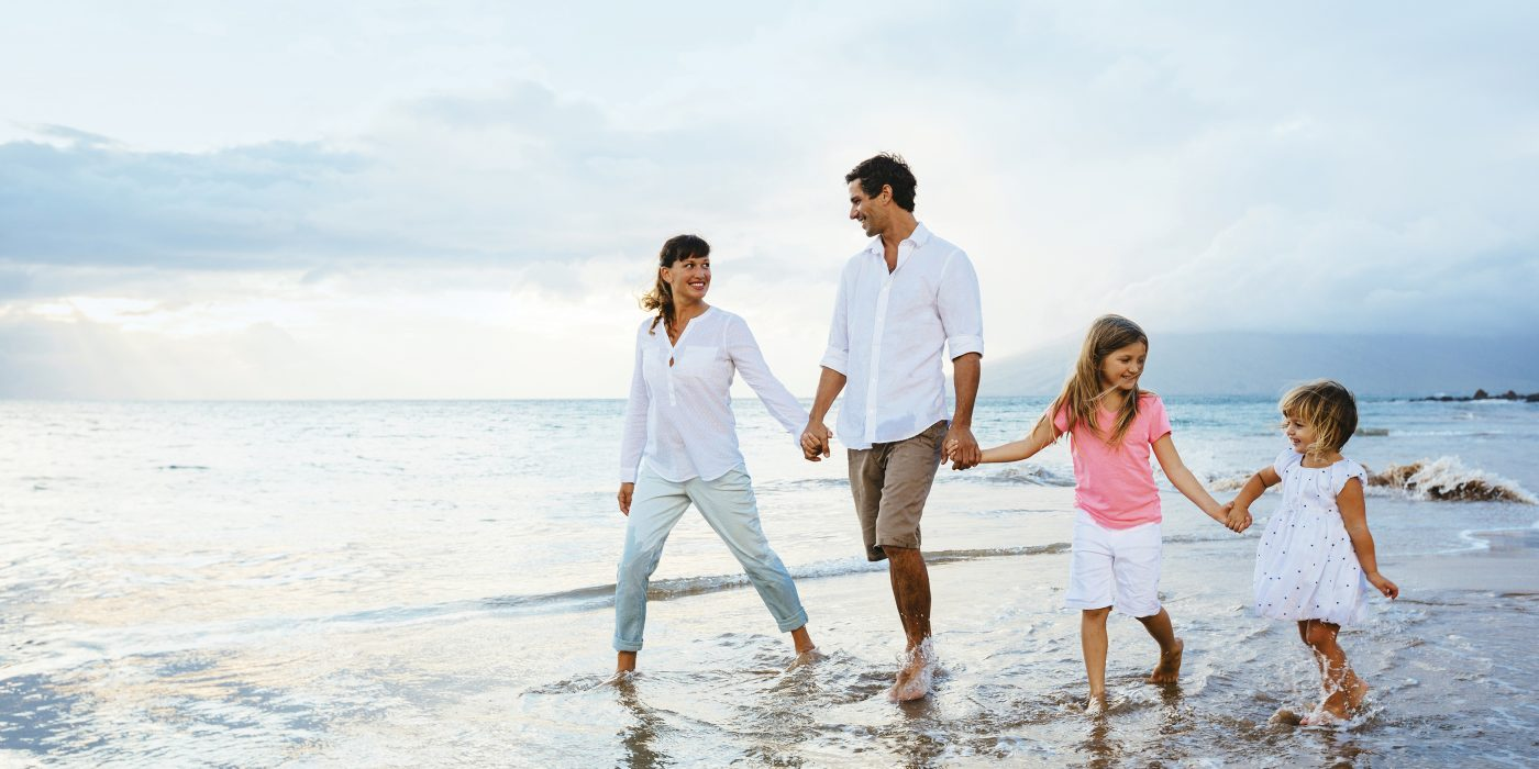 Family walking on beautiful beach