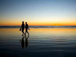 Romantic couples walks on beach during susnet