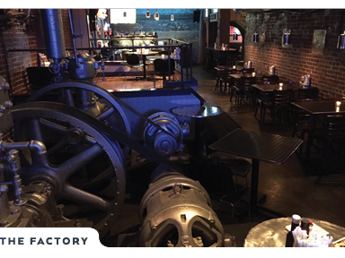 Restaurant dining tables, and full bar shown beyond restored and retired factory machinary.