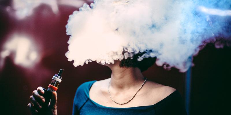 Woman's face hiden by Vape Cloud