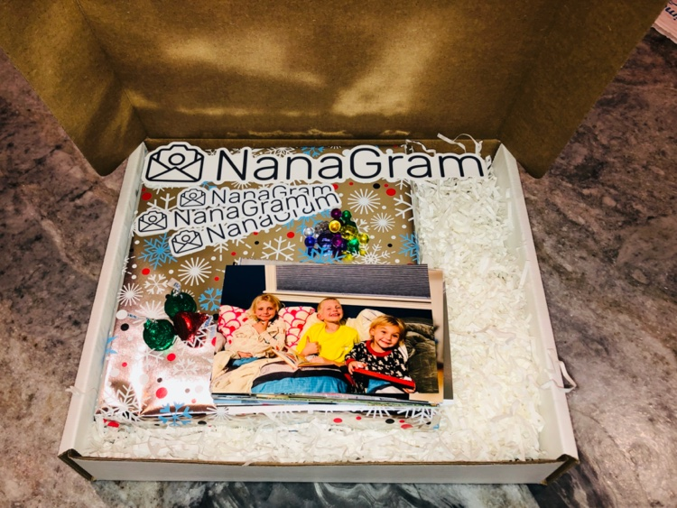 A wrapped photo album in a box looking pretty with magnet pins, photo of 3 kids, and Hershey Kisses
