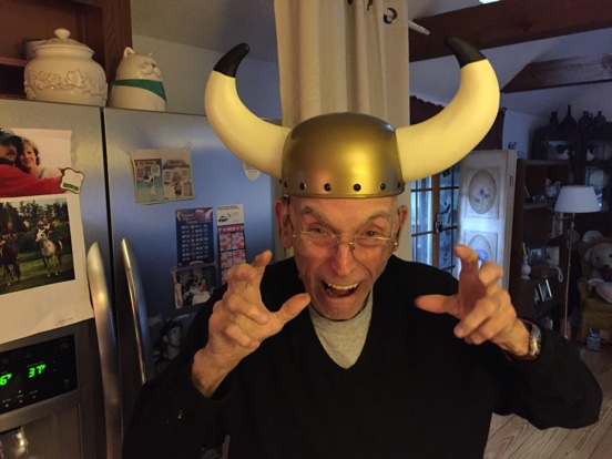 A man (Grandpa Cook) in his 90s wearing a viking hat and making a funny face.