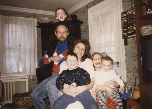 Mid 90s family photo, crammed together on a chair.