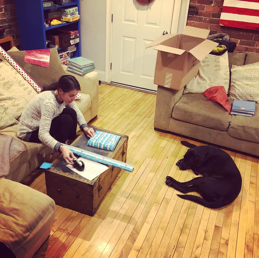A woman on a couch wrappnig photo albums with a dog laying on the floor
