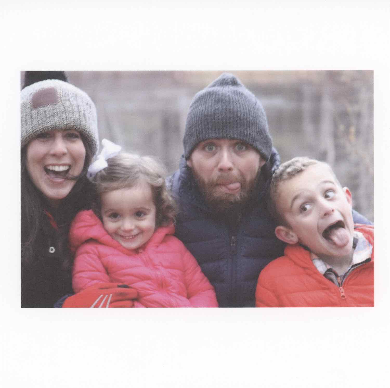 Scan of a photo of adults and two kids in a fun portrait. They're all wearing winter coats. The  adults are wearing winter hats. On the left is a young, beautiful, brunette woman smiling big, wearing a light brown winter hat with a leather patch. A cute little girl is to her right, they're all close together, wearing a pink puffy jacket with a white bow in her dirty blonde hair. Next to the girl is a man wearing a blue winter hat and a navy puff jacket, his tongue slightly sticking out and his beard a brown-red. To the man's right is a boy, a few years older than the girl, wearing a red puffy jacket and a flannel under it, his tongue fully out and his eyes wide. They're all having a blast.