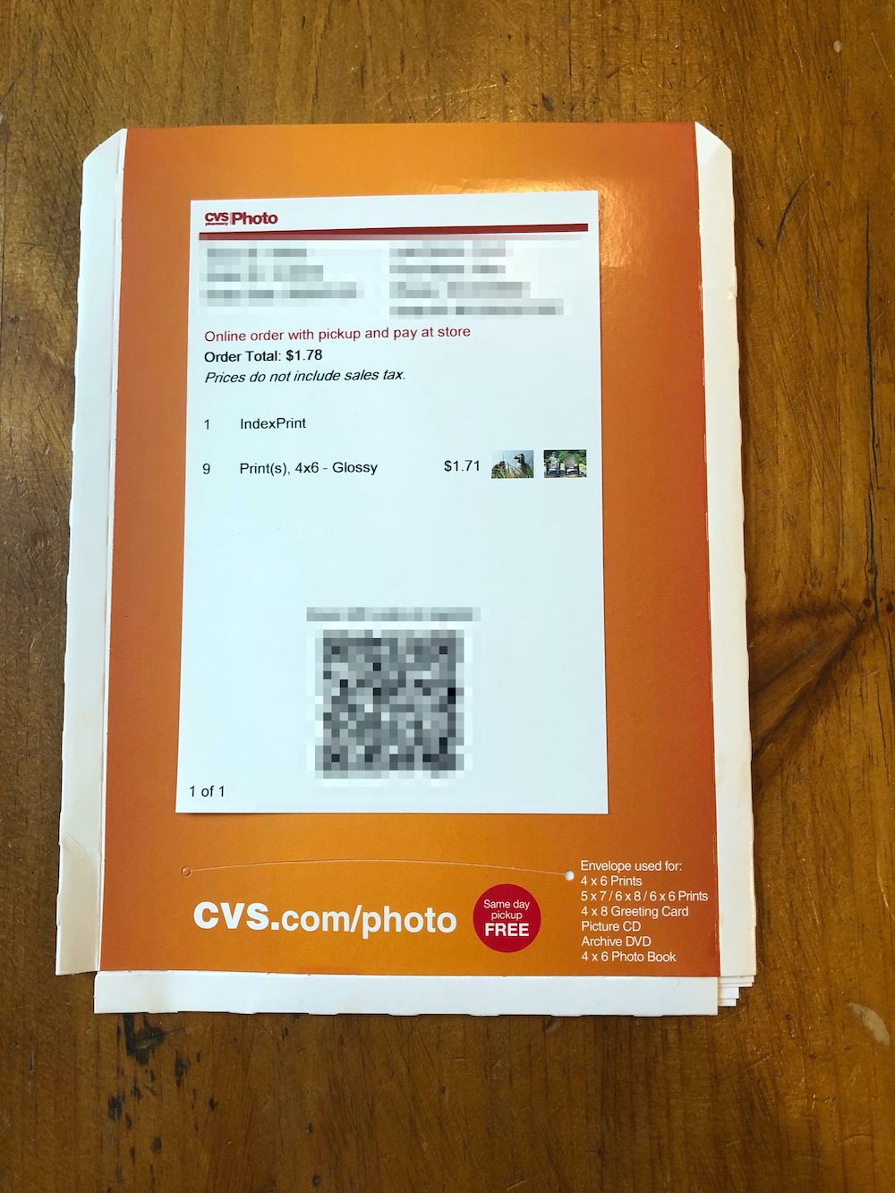 "Orange and white envelope with a white 4x6 receipt stuck on the center. At the top of the receipt is the CVS Photo logo and a red bar. Below that is some blurred text. Below that is red text reading ""Online order with pickup and pay at store"" followed by black text reading ""Order Total: $1.78m, Prices do not include sales tax."" Then, two lines reading ""1. IndexPrint 9. Print(s) 4x6 Glossy $1.71"" followed by two thumbnail images of a bird and a man sitting on a chair with trees behind him. A blurred out QR code. At the bottom of the envelope in white and red text over the orange reads ""CVS.com/photo"" in large text followed by smaller text on the lower right: ""Envelopes used for: 4x6 prints, 5x7, 6x8, 6x6 Prints, 4x8 Greeting Card, Picture CD, Archive DVD, 4x6 Photo Book."" The envelope is positioned vertically. It's not a perfect rectangle: The corners are kind of a cut out triangle on the top and missing small squares in the lower corners, likely due to some kind of folding.  Envelope sitting on wood table top."
