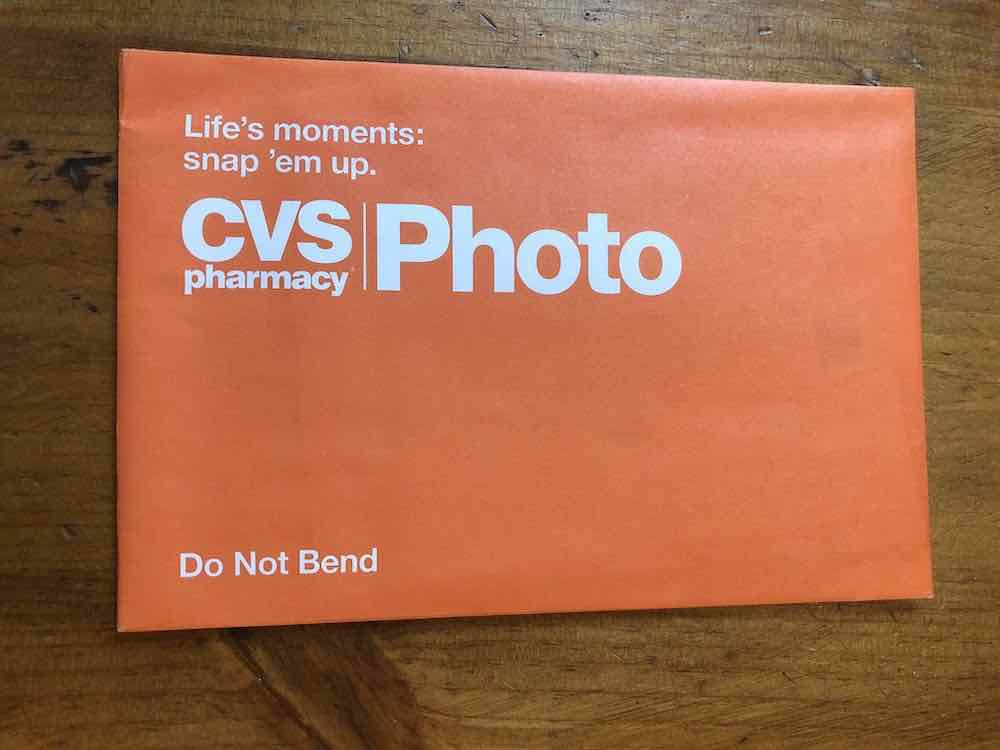 """An orange catalog envelope horizontally positioned on a wooden surface. The top left corner begins some text that reads """"Life's moments: snap 'em up."""" Below is a bigger text: """"CVS pharmacy"""" stacked on each other, the """"pharmacy"""" in smaller fonts. There is a thin horizontal line, on the right side of the line is larger text, it reads, """"Photo."""" At the bottom left is a warning: """"Do Not Bend."""" All text printed on the orange surface is white.  Envelope sitting on wood table top."""