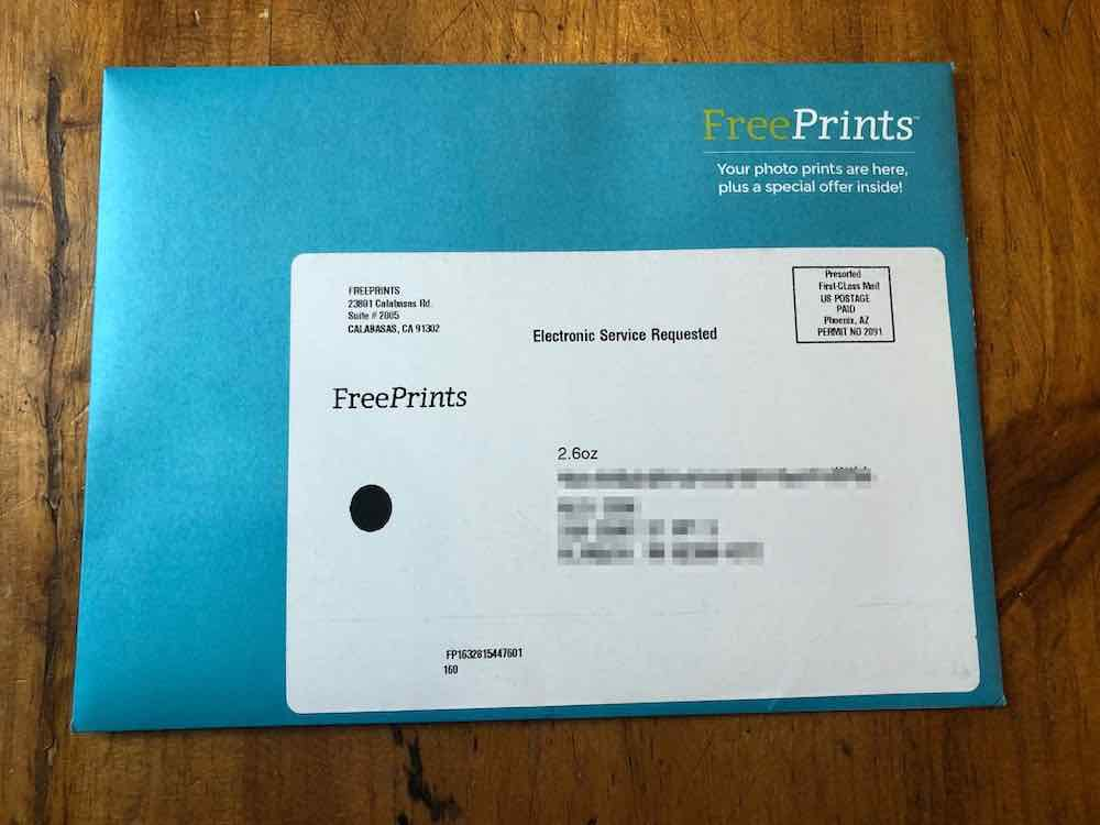 """A teal wallet envelope is placed horizontally on a wooden surface. At the top right corner has text that says """"FreePrints,"""" under this is a thin line, then under the line, a text says """"Your photo prints are here, plus a special offer inside!"""" The text is in white, except """"Free"""" which is in yellow. A large mailing label covers most parts of the envelope. The left side of the shipping label has a return address in black ink that says """"FREE PRINTS, 23801 Calabasas Rd. Suite # 2005, CALABASAS, CA 91302."""" A text in black the middle reads """"Electronic Service Requested."""" A postage stamp at the top right corner says, """"Presorted First-Class Mail, US POSTAGE PAID. Phoenix, AZ. PERMIT NO 2091,"""" the text is in a box. The left-hand corner has large text, that is also the logo: """"FreePrints"""" in black print. The middle of the label is where the digitally blurred delivery address sits, right on top of it is a text that states the size of the envelope: """"2.6oz."""" A black blot is at the left side of the address, its function is not known. The bottom left contains text that reads, """"FP1632815447601,"""" right under this is the number """"160."""" Envelope sitting on wood table top."""