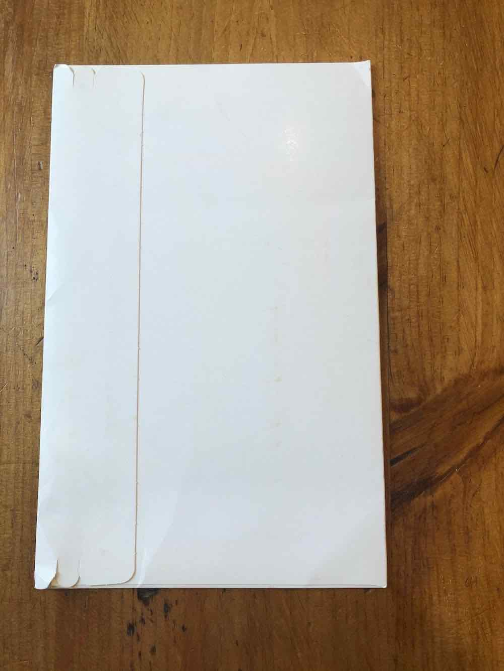 A vertically positioned white wallet sealed envelope, with its flap by the left-hand side, and small incisions at the edges of the flap. Envelope sitting on wood table top.