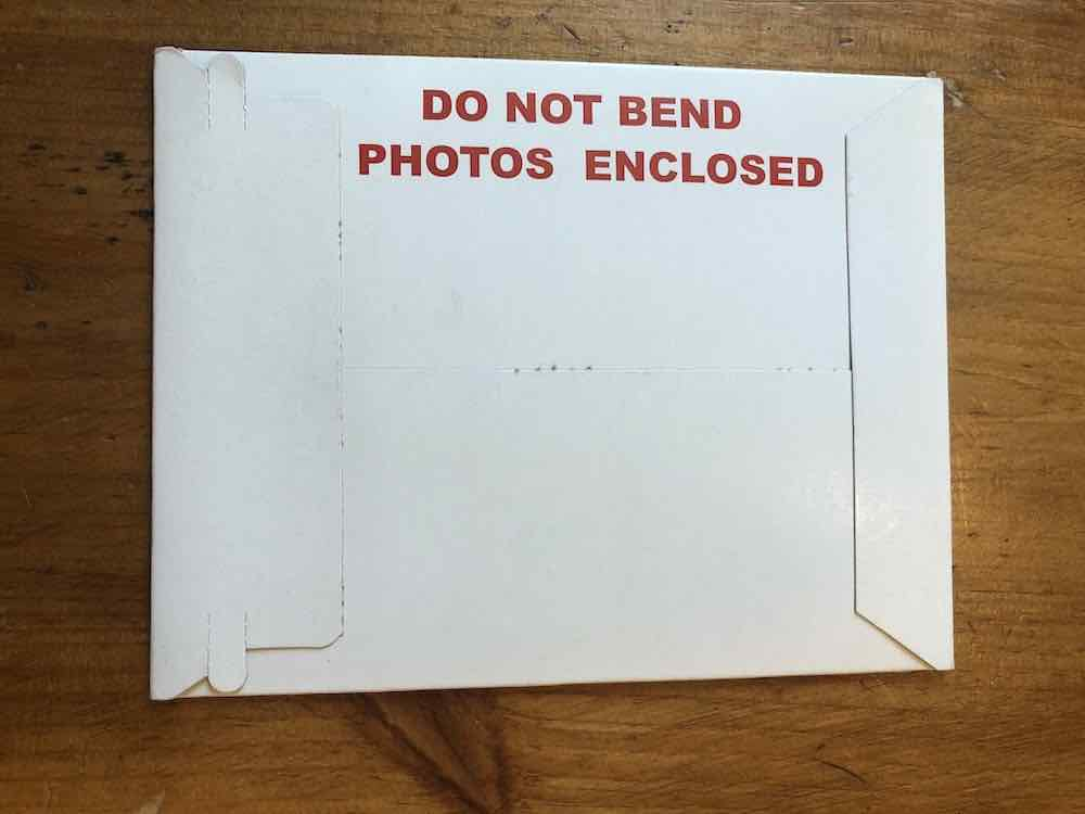 "A white catalog envelope horizontally positioned on the wooden surface. There are two flaps on the left and right. The flap on the left is peculiar, it has some tabs at each end. At the right corner of the envelope is vertically printed text with a warning in large red letters that say ""DO NOT BEND PHOTOS ENCLOSED."" The rest of the envelope is plain. Envelope sitting on wood table top."