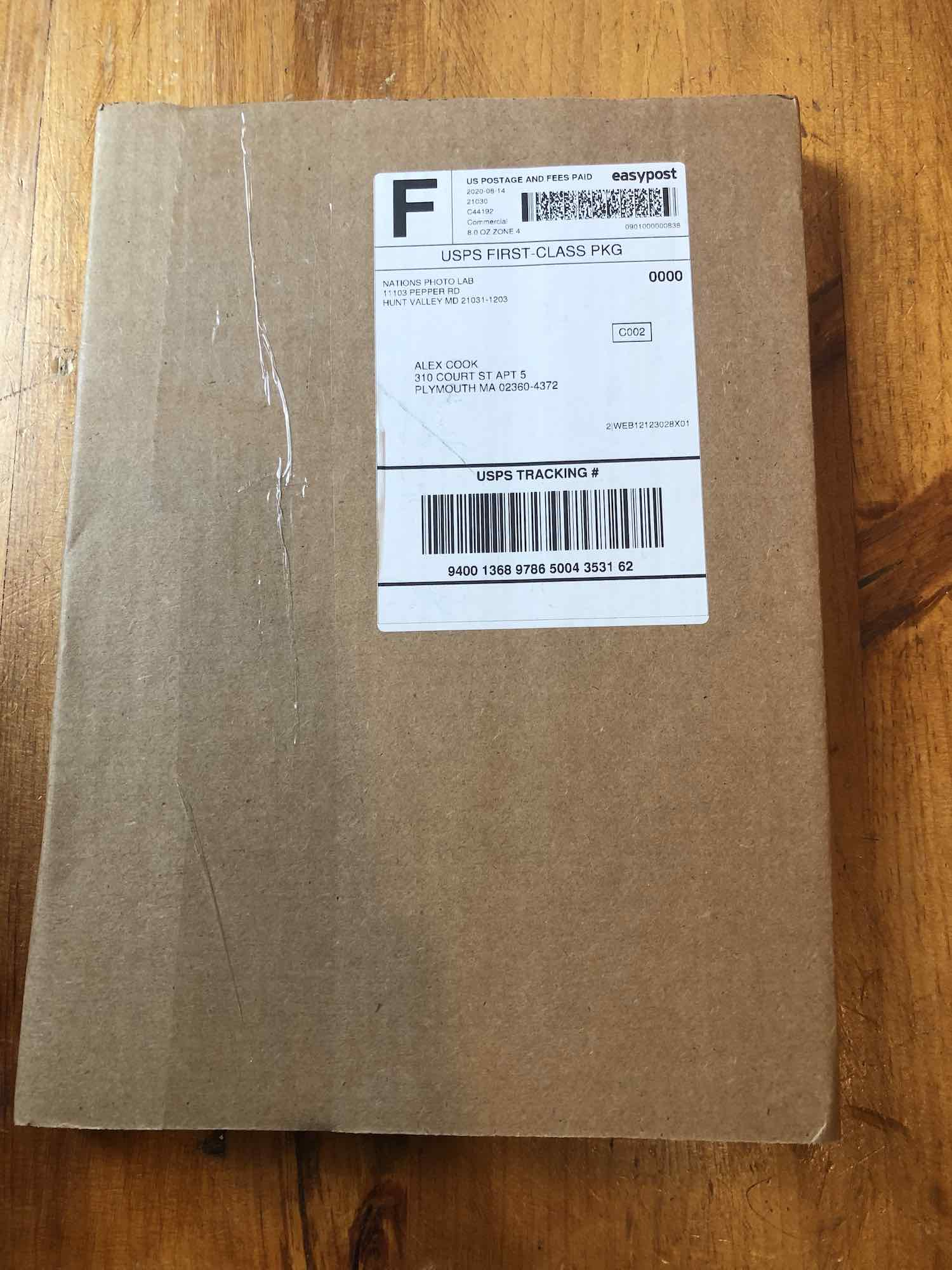 "There is a brown cardboard box wallet envelope vertically positioned on a table. There is a transparent adhesive tape wrapped around the left side of the box. The top right side of the box has a shipping label stuck to it. The shipping label is divided into 5 horizontal parts. The first part of the shipping label is divided into two parts by a vertical line. The left contains a block letter ""F"" printed in a very thick font. The right part has the postage information. It reads ""US POSTAGE AND FEES PAID,"" under this is some text in smaller fonts, it reads, ""2020-08-14 21030 C44192 Commercial 8.0 OZ ZONE 4."" Across this is a text in slightly larger and thick fonts it says ""EasyPost."" Under this is a barcode, and below the barcode are tiny numbers that say ""0901000000838."" The second part has text in block letters that reads ""USPS FIRST-CLASS PKG."" The third part has more space than the other parts. In it, there is a return address printed in the top left corner. It reads, ""NATIONS PHOTO LAB, 11103 PEPPER ROAD, HUNT VALLEY MD 21031-1203,"" right across are digits that say, ""0000."" Below the return address is the delivery address which is blurred out. To the top right of the delivery address is the text ""C002"" printed in a small box. At the bottom right corner of this part is some reference number that read ""2