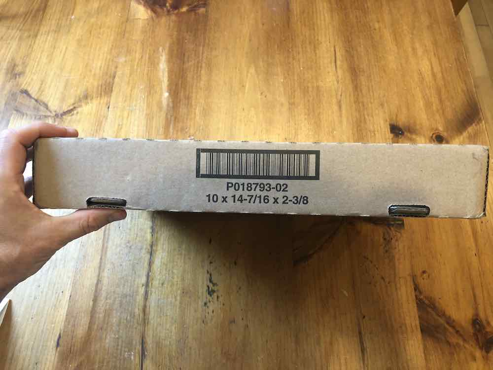 "A hand holds up a brown box about 3"" high on its side. The side facing the camera shows the edges are serrated all around with two rectangular holes at the bottom, about 5 inches apart. The side facing up has a barcode printed in black, the dimensions of the box are printed are the bottom of the barcode. It reads, ""P018793-02, 10x14-7/16 x 2-3/8."" Envelope sitting on wood table top."