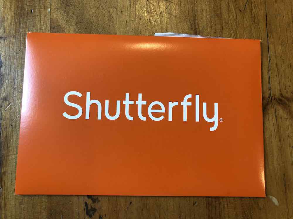 Orange envelope positioned horizontally. In the center, in large white sans-serif font it is the shutterfly logo. The logo is text-only with no other icons. At the top of the envelope a label from the other side sticks out. Envelope sitting on wood table top.