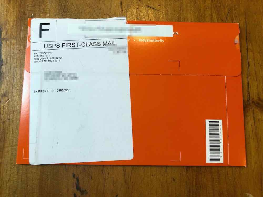"Orange envelope with white sticker covering the left side. The sticker has a large F in the upper left: No idea what F means. Below that it reads ""USPS FIRST-CLASS MAIL. "" surrounded above and below by two thin black lines. Below that is a return address: ""Shutterfly Inc, Returns Team, 5005 Deans Lake Blvd Shakopee, MN 55379."" The shipping address is blurred out. Below that it reads ""SHIPPER REF: 199980958."" To the right of the label is white text on the orange envelope: ""#MyShutterfly."" In the lower right hand corner of the envelope is a bar code with some random numbers, positioned vertically. Envelope sitting on wood table top."
