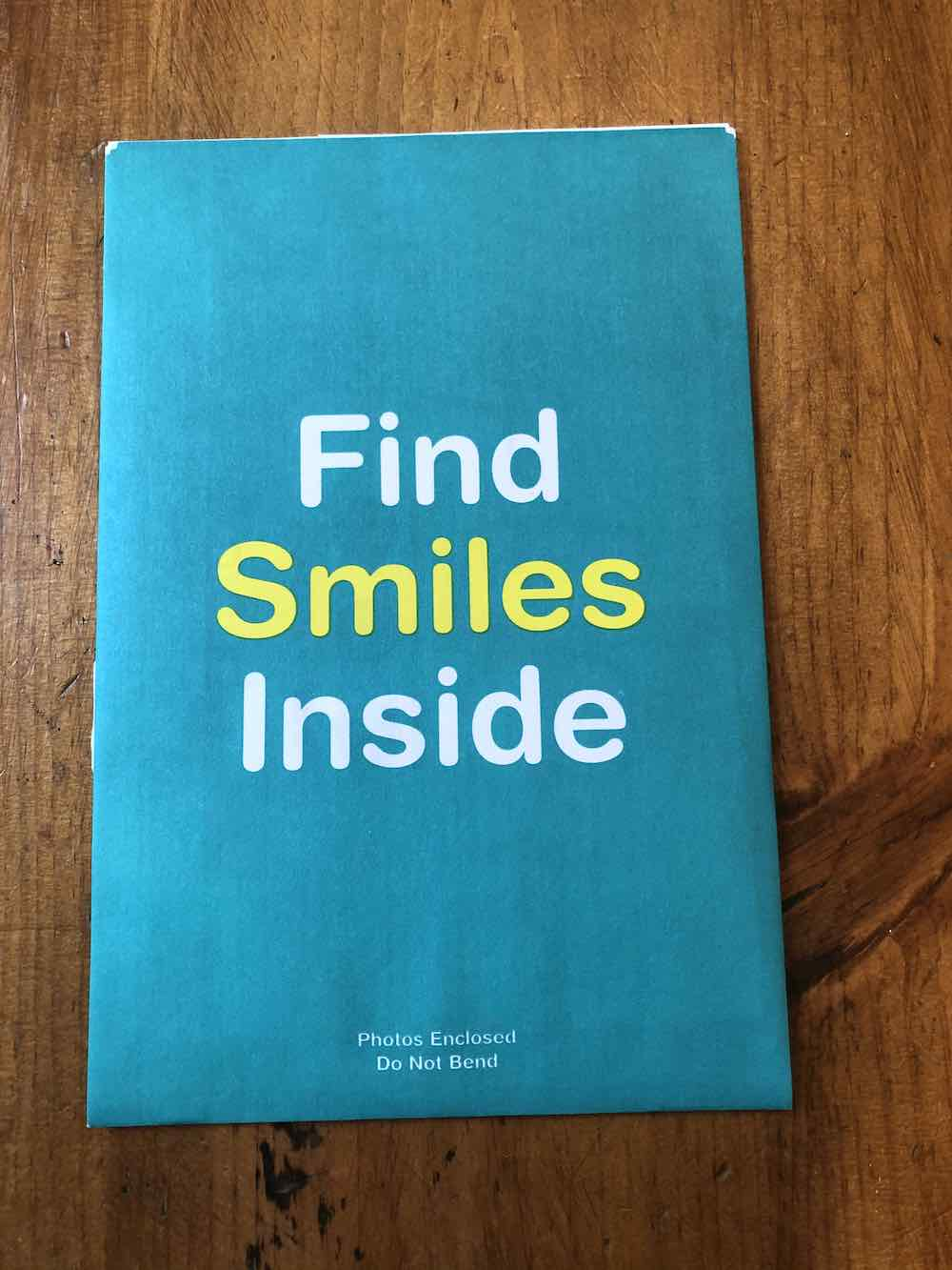 "This envelope is all teal on the back. In a large font taking up about 30% of the envelope, centered, it reads ""Find Smiles Inside"" with Find and Inside in white and Smiles in yellow; each word stacked on top one another. At the very bottom in the center, in white text it reads ""Photos Enclosed Do Not Bend."" Envelope sitting on wood table top."