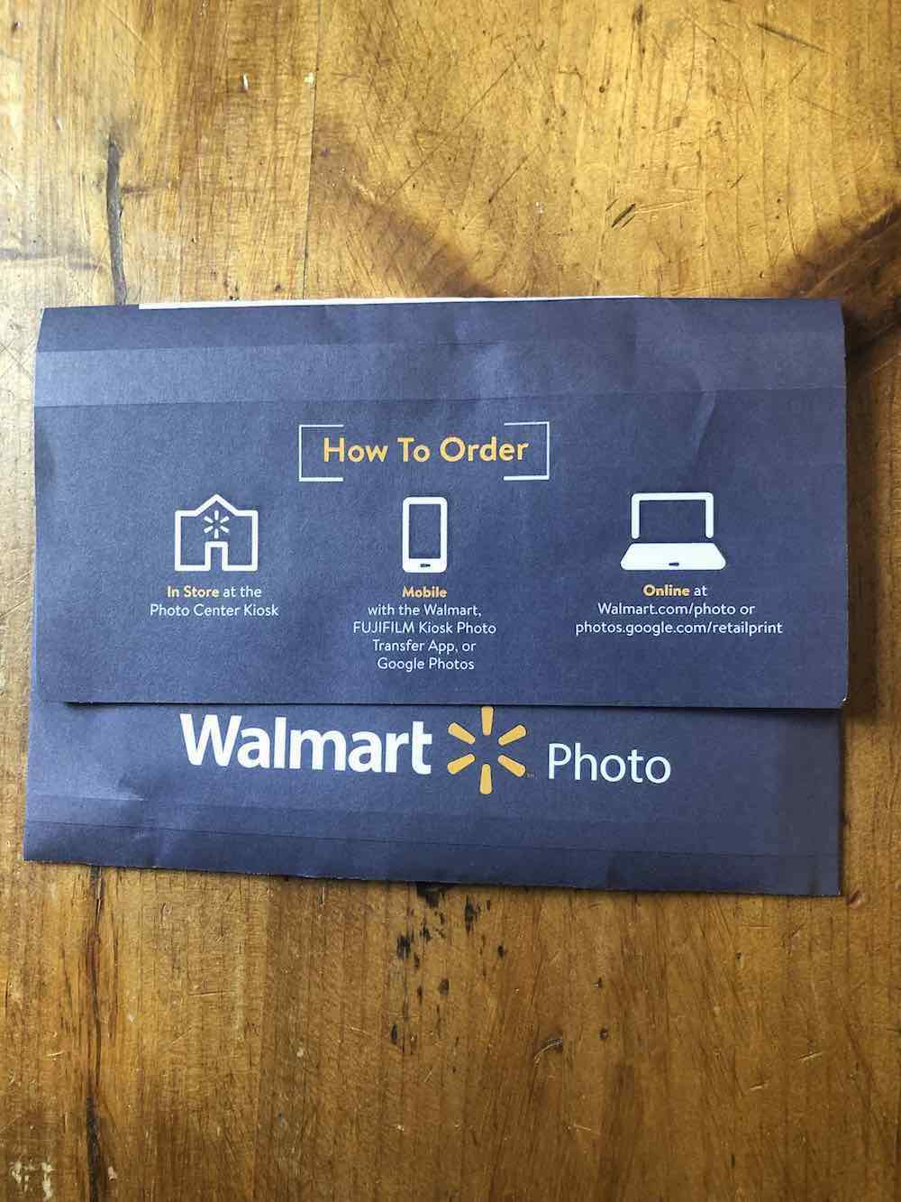 "A navy blue wallet envelope is positioned horizontally on a wooden surface. The flap is larger and covers over half of the envelope. The flap has some information on it; at the top center of the flap has yellow text and white brackets that read, ""How To Order."" Below are three icons: A store, a mobile phone, a laptop, all in white print. And printed horizontally on the flap. From the left, has the store icon and text under it that says, ""in Store"" printed in yellow, the remaining text is in white and it reads, ""at the Photo Center Kiosk."" The mobile phone icon is at the center, under it is text in yellow that reads ""Mobile,"" and some more words that say, ""with the Walmart, FUJIFILM Kiosk Photo Transfer App, or Google Photos"" in white text. The laptop icon is on the right, the text under it begins with ""Online"" in yellow text, and continues the text in white that reads"" at Walmart.com/photo or photos.google.com/retailprint"" printed in white. Below the flap, on the envelope is a large print that reads ""Walmart Logo"" with the ""Yellow logo"" between both texts. The ""Walmart"" is printed in a larger font. Envelope sitting on wood table top."