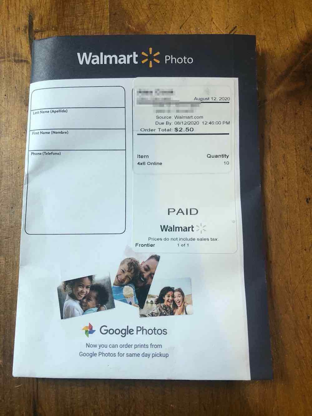 "A navy blue wallet envelope with most of the front in white. The top part has white text that says ""Walmart Photo"" with the Walmart's logo in yellow in between these two words and the ""Walmart"" in bold text. Below is the beginning of the white part. On the left side is a box with rounded-off edges. It contains three lines. Under the first line is a text with the Spanish translation in brackets that reads, ""Last Name (Apellido)."" Under the second line is a text that reads, ""First Name (Nombre)."" Under the third line, it says ""Phone (Telefono)"" and there is a long black space under the third line that increases the length of the box. The text in the box is printed in black. On the right side, there seems to be a placeholder under; two white stickers are on it. The first sticker is the shipping label and the top left corner is blurred. Across there is a date that says ""August 12, 2020."" Then a thick black line. Under it, some blurred text, under the blur is a text that says, ""Source: Walmart.com, Due By 08/12/2020 12:46:00 PM, Order Total: $2.50."" Another thick line, beneath the line, is text in a table format. The text on the left says ""Item"" opposite it reads ""Quantity."" Under ""item"" it says ""4x6 Online"" and the corresponding text below the ""quantity"" is ""10."" The second sticker is right below the first one, with ""PAID"" in large fonts at the center. Below is the text ""Walmart"" and the Walmart logo in faint black and white print. There is a text below that reads, ""Prices do not include sales tax."" At the bottom left of this sticker is the word ""Frontier"" and across it is the text ""1 of 1."" All the text on the stickers were printed in black. At the bottom of the white part of the envelope are three photos printed like they were spread on one another. The first picture on the left has a girl of about 7 or 9 years old, hugging a boy who seems to be 5 or 6 years old, presumably siblings and both smiling at the camera. The photo in the middle has a man and a young boy smiling, the boy seems to be sitting on the man's lap, it is not certain as the photo is a close-up shot; The boy is holding a cone of ice cream. The last photo on the right has two ladies smiling at the camera, presumed to be friends and on a vacation. Below this photo is Google Photos logo of orange, red, green, and blue, and right in front says ""Google Photos,"" The former is in much bolder font. There is message under the reads, ""Now you can order prints from Google Photos for same day pickup."" Envelope sitting on wood table top."
