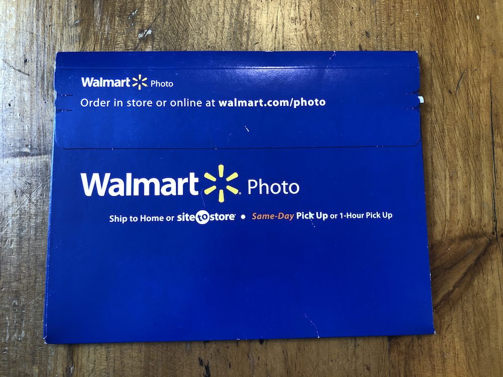 "Navy blue envelope with flap on the top quarter. Walmart Photo logo appears twice on the top and bottom. Above the top logo on the flap it reads ""Order in store or online at walmart.com/photo."" Below the larger logo towards the center of the envelope it reads ""Ship to Home or site-to-store — Same-Day Pick up or 1-Hour Pick Up."" Envelope pull tab on upper-right and flap unopened. Envelope sitting on wood table top."
