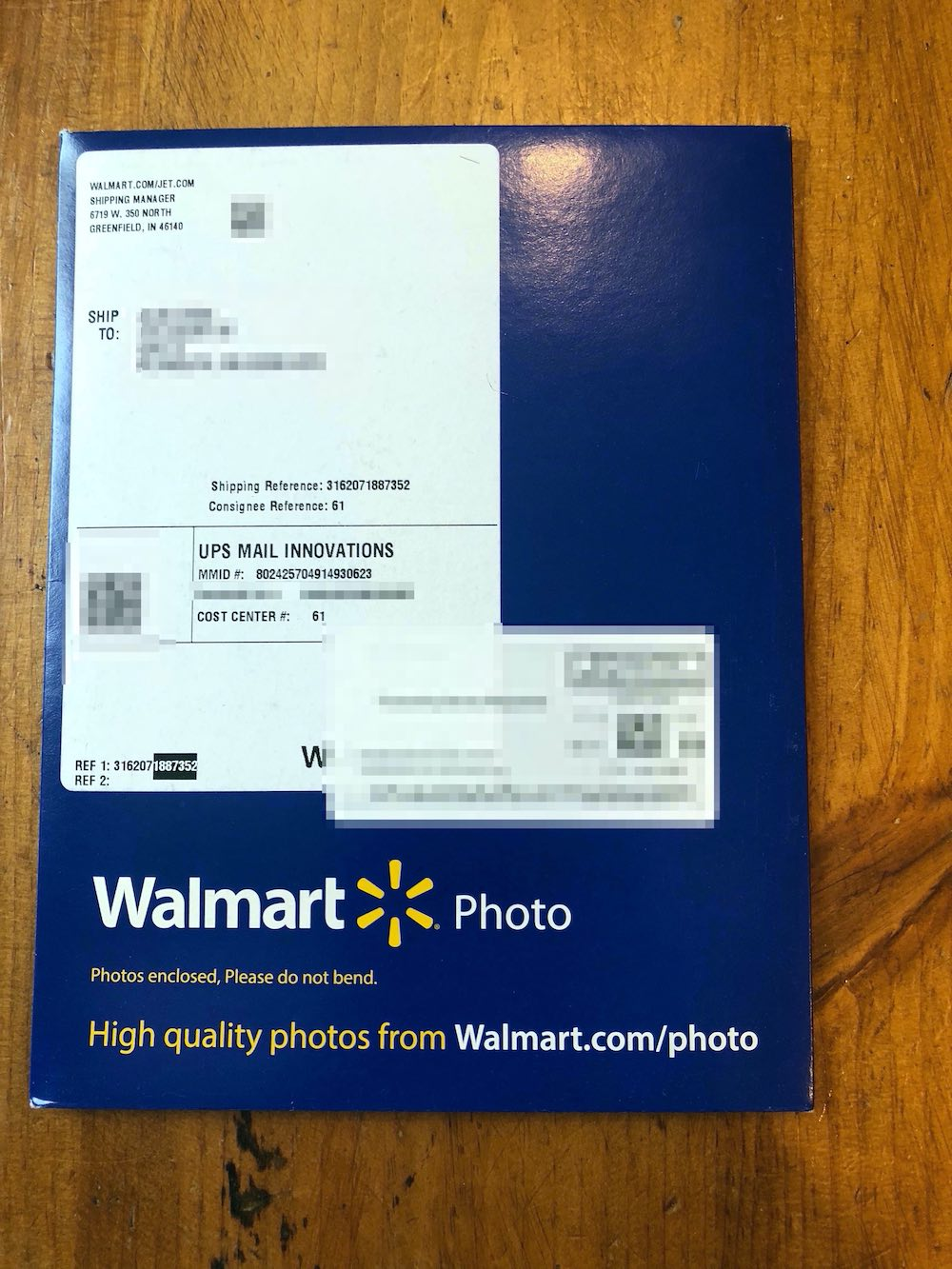 "Navy blue envelope with white mailing sticker by UPS Mail Innovations. Return address is Walmart.com in Greeinfield, IN. Personal shipping details blurred out. On the bottom of the envelope is the Walmart Photo logo in white and yellow. Below that it reads ""Photos enclosed, Please do not bend,"" and then ""High quality photos from Walmart.com/photo."" Envelope sitting on wood table top. Envelope sitting on wood table top."