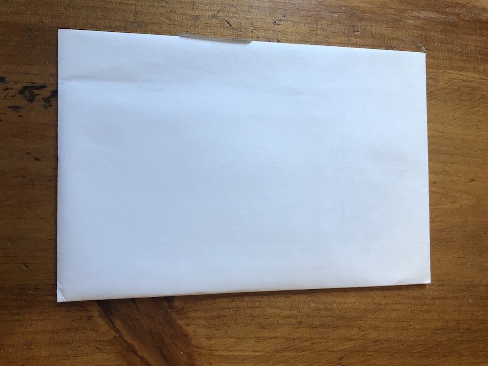 A blank white catalog envelope placed horizontally. Envelope sitting on wood table top.