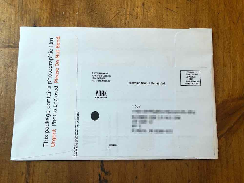 "White envelope positioned horizontally, with two flaps at both ends. The flap on the left has text in red and black letters which read: ""This package contains photographic film. Urgent Photos Enclosed Please Do Not Bend."" Right under the flap are tiny black illegible text; the flap covers most of the words. There is a large white shipping label on the back of the envelope with texts all in black letters. A return address sits at the top left corner. It reads: ""Shipping Manager, YorkPhotoslabs.com 10550 Ewing Road, Beltsville, Maryland, MD 20705."" At the top right corner of the label is a postage stamp: ""Presorted First-Class Mail / US Postage Paid Capital Hgts, MD, Permit No 5208."" The top center of the label is a text that reads: ""Electronic Service Requested"". There is a slightly blurred YorkPhotos.com logo under the return address. The center of the label has text that says 1.5oz, and a digitally blurred shipping address. At the bottom, left of the label are tiny numbers that say: 7901411-1-11.  Envelope sitting on wood table top."