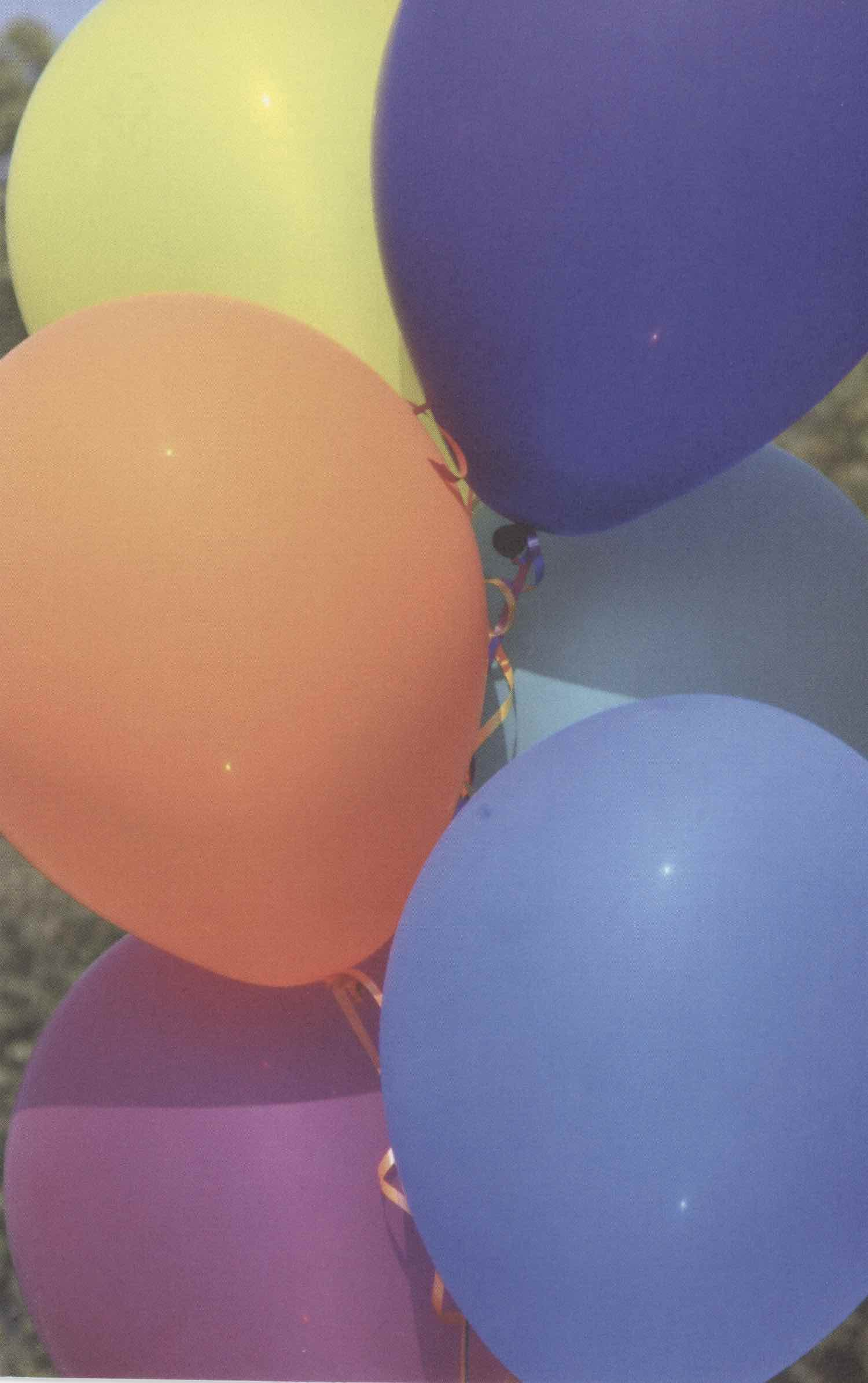 Scanned photo of birthday balloons. The photo is zoomed in with 95% of the photo being balloons. It's positioned vertically. There are 6 balloons in the photo. Upper-left: Yellow, upper-right: Dark blue/purple, then orange, teal, magenta, and blue. All of the balloons have curly orange ribbons.