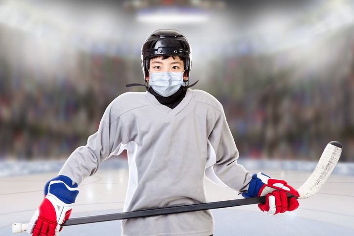 Boy suited up to play ice hockey wearing mask
