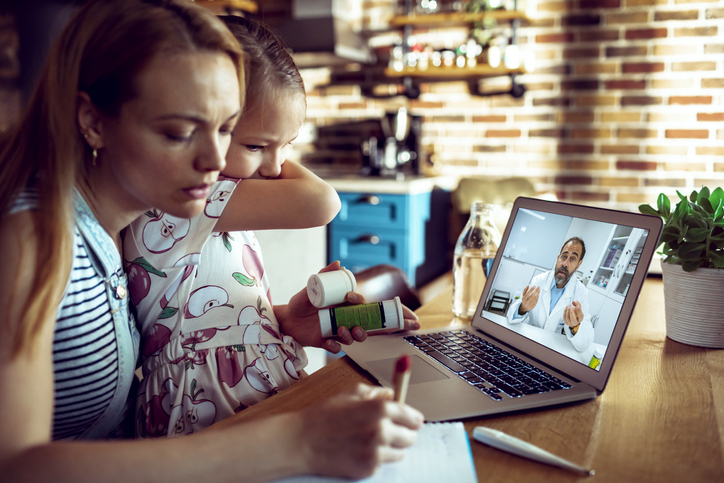 Close up of a mother and daughter consulting with their doctor over a video call on their laptop