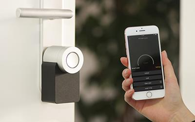 A person holds up a smartphone to a smart keyless entry lock on a door.