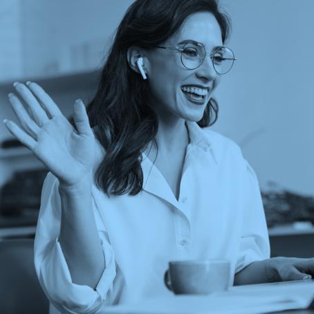young women at laptop waving