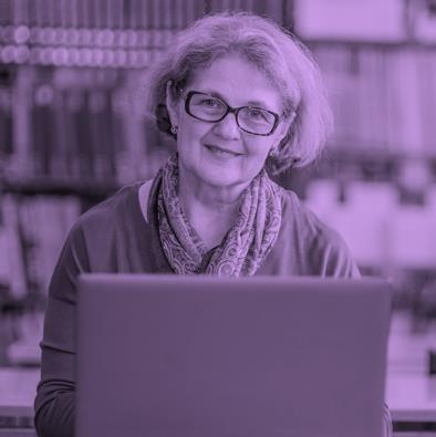 Women with glasses in front of a computer, with books in the background