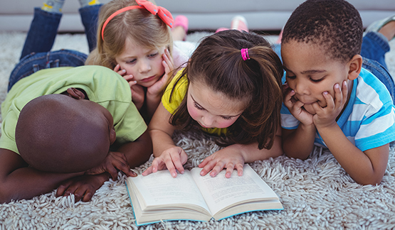 Four kids huddle around one book