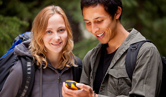 Two college kids using a GPS to find a geocache