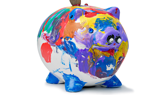 A brightly colored piggy bank receives a quarter.