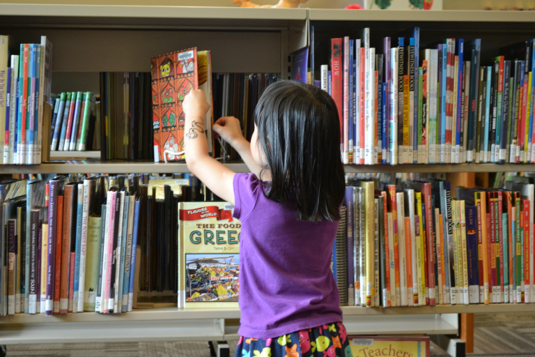 Young Child selecting a book from a crowded shelf