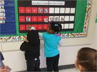 Young children using a rekenrek chart for attendance.