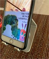 iPhone on stand showing cover of The Very Hungry Caterpillar