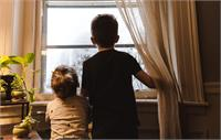Siblings standing by window